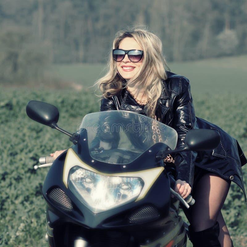 Blondevrouw in zonnebril op een sportenmotorfiets royalty-vrije stock foto's
