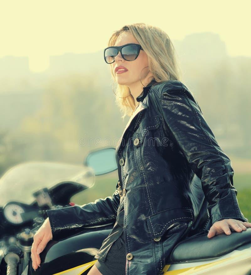 Blondevrouw in zonnebril op een sportenmotorfiets stock foto
