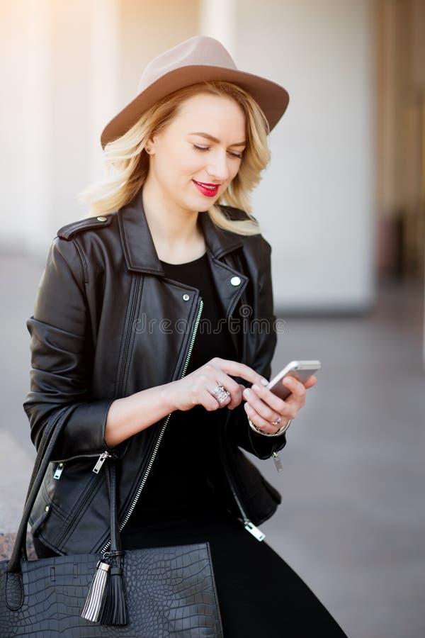 Blondevrouw in zwart hoed en leerjasje en zak die de mobiele telefoon met behulp van royalty-vrije stock foto's