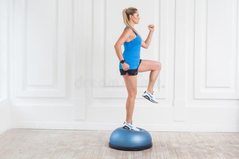 Blondevrouw in zwarte borrels en blauwe bovenkant die in gymnastiek die exersice in de trainer van het bosusaldo, opgeheven één k stock foto's