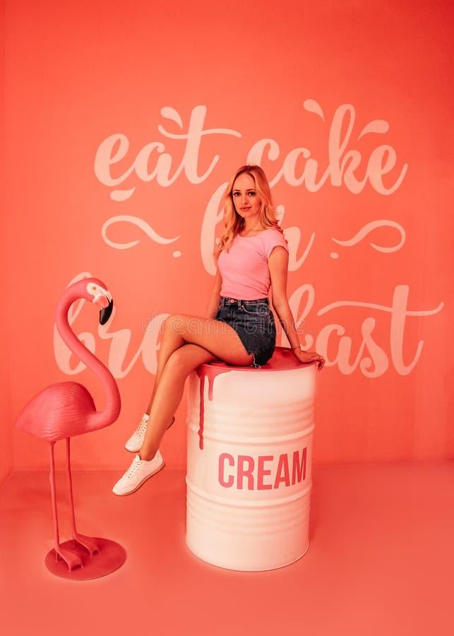Blondie bonito novo que senta-se em uma sala com cenário em um fundo do pêssego e em um flamingo cor-de-rosa foto de stock royalty free