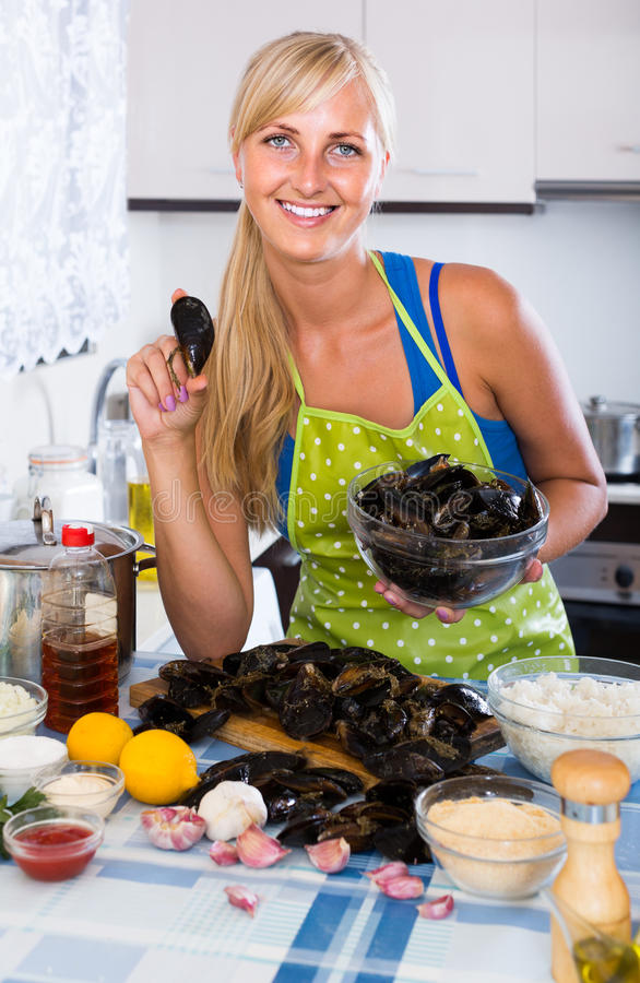Blondie, das mit frischen Miesmuscheln in der Küche aufwirft stockbild