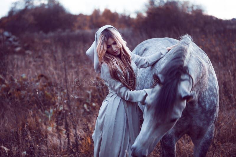 blondie de beauté avec le cheval dans le domaine, effet de la tonalité photos stock