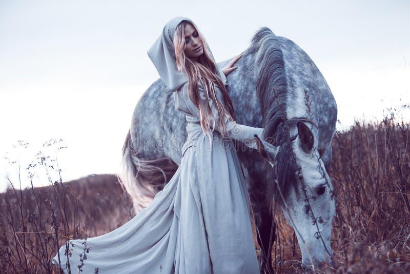 blondie de beauté avec le cheval dans le domaine, effet de la tonalité photographie stock libre de droits