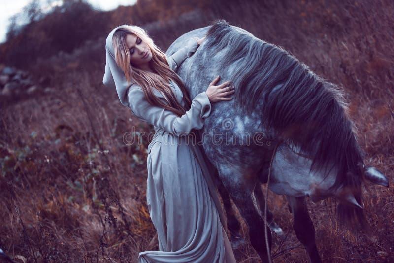 blondie de beauté avec le cheval dans le domaine, effet de la tonalité photo stock