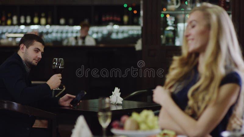 Blondie flicka som ser mannen i restaurang från ett annat ställe