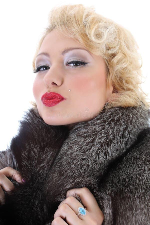 Blondie Frau mit dem Pelzkragenküssen lizenzfreie stockfotografie