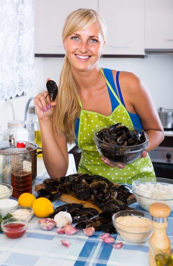Blondie het stellen met verse mosselen in keuken stock afbeelding