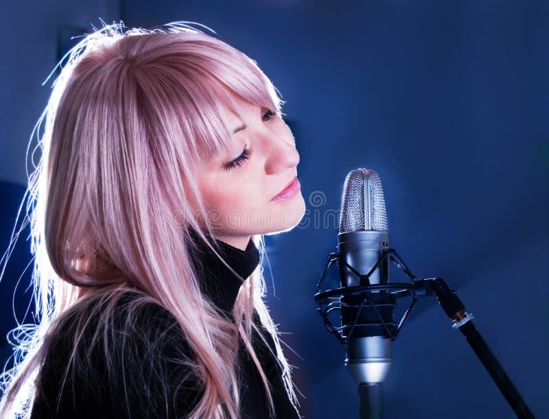 Blondie mit Mikrofon lizenzfreie stockfotografie