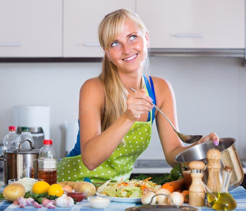Blondie préparant des veggies dans la cuisine photos stock