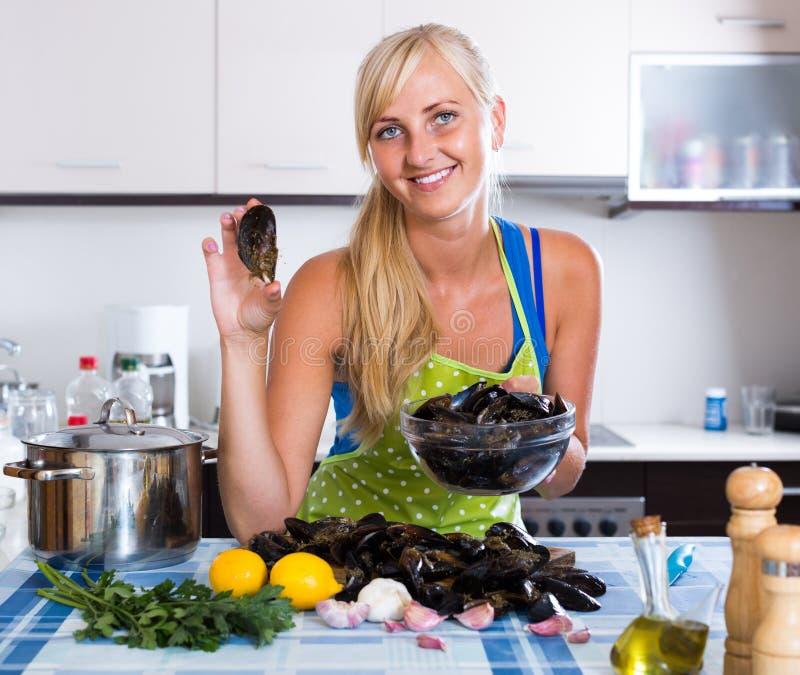 Blondie que presenta con los mejillones frescos en cocina foto de archivo