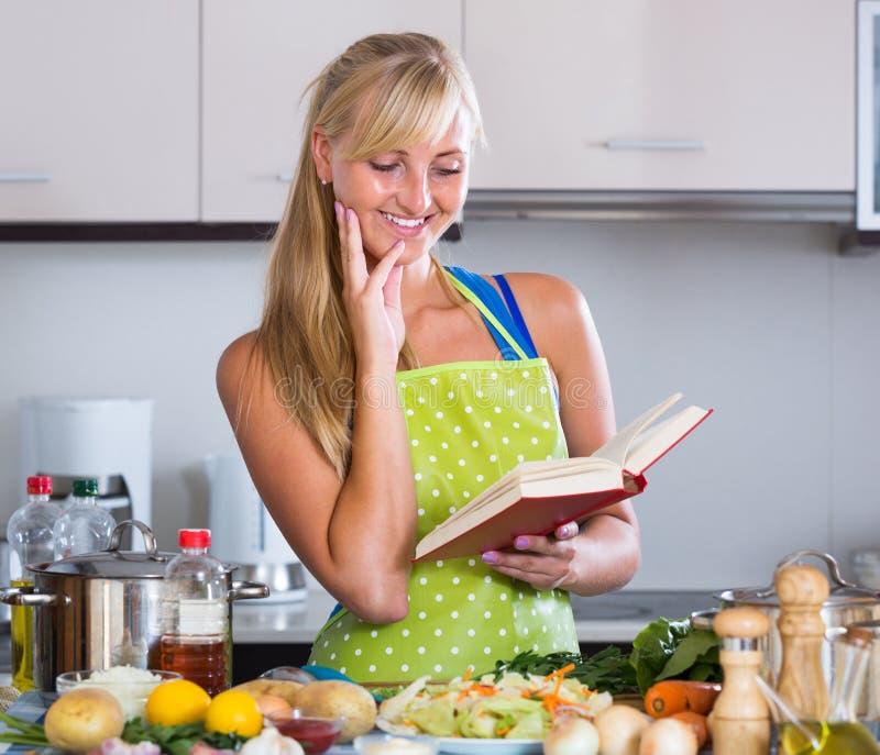 Blondie som förbereder veggies i kök royaltyfria bilder