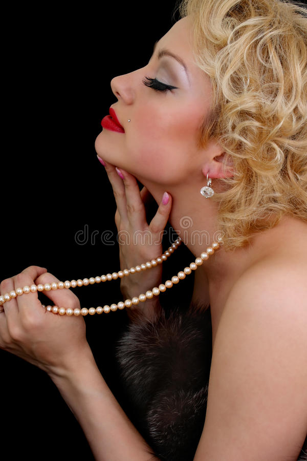 Blondie woman with pearl necklace in hand dreaming royalty free stock photography