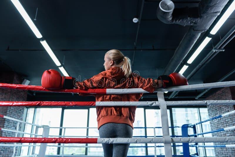 Blondin-haired kvinnlig boxare som bär grå damasker och det röda sportomslaget royaltyfri bild