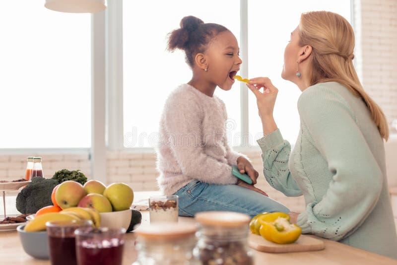 Blondin-haired moder som matar hennes gulliga roliga flicka med frukter fotografering för bildbyråer
