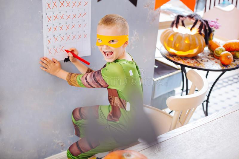 Blondin-haired pojke som bär dräkten för Ninja sköldpaddaallhelgonaafton som känner sig galen royaltyfri fotografi