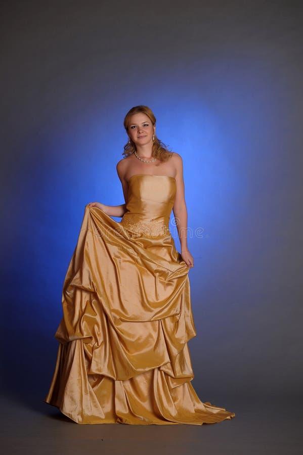 Blondin i en elegant guld- klänning fotografering för bildbyråer