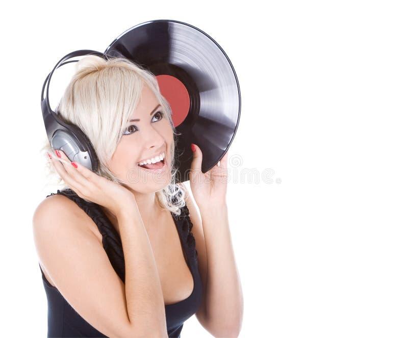 Blondin i hörlurar med vinylrekordet över vit arkivbilder