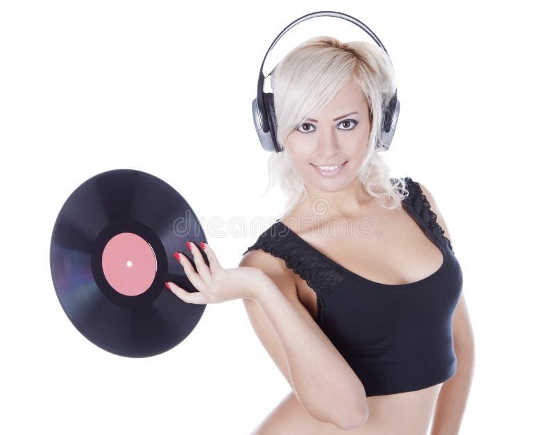 Blondin i hörlurar med vinylrekordet över vit arkivfoton