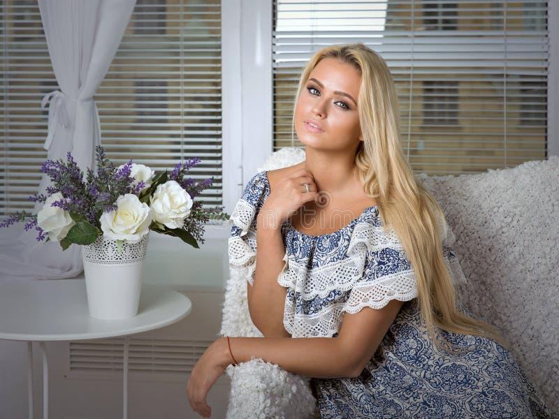 Blondin i klänningsammanträde mot fönstret arkivbild