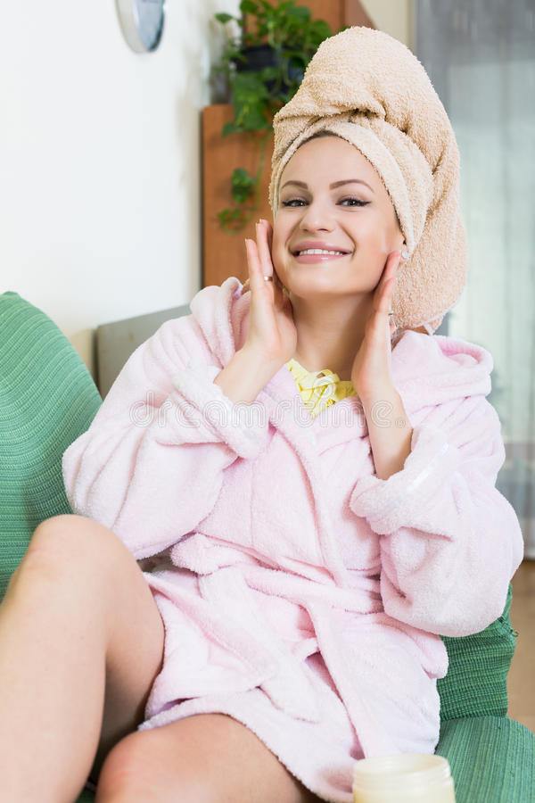 Blondin med ansiktsmask som inomhus kopplar av på soffan arkivfoto