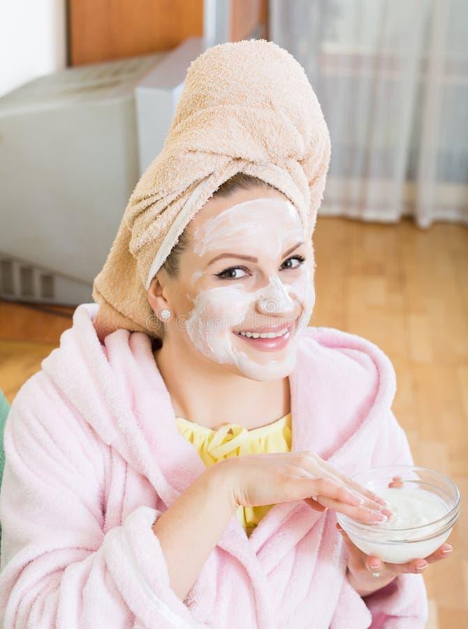 Blondin med ansiktsmask som inomhus kopplar av på soffan royaltyfria foton