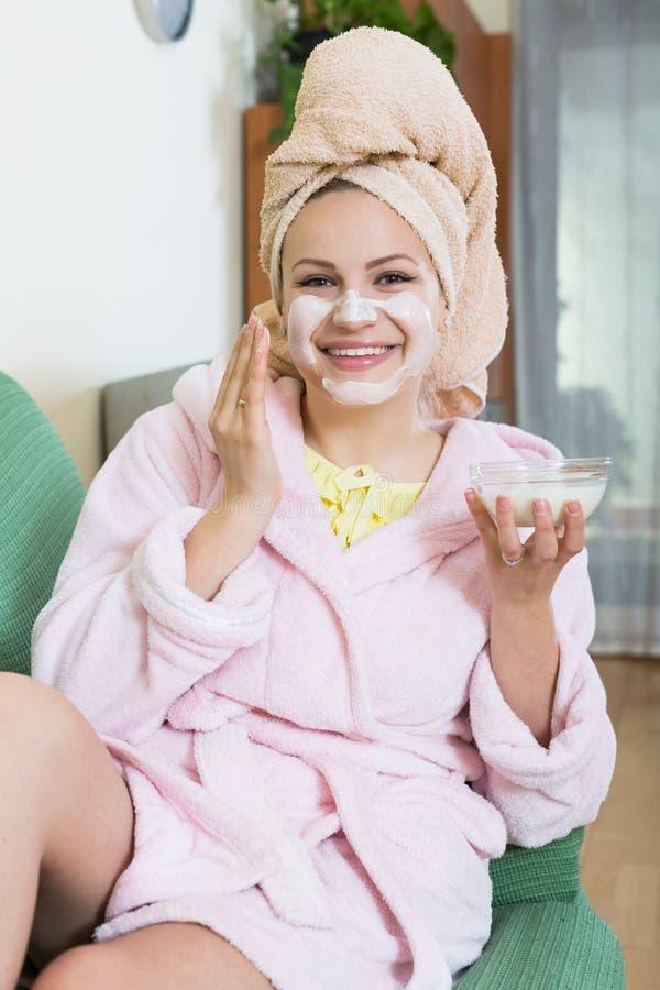 Blondin med ansiktsmask som inomhus kopplar av på soffan arkivbilder