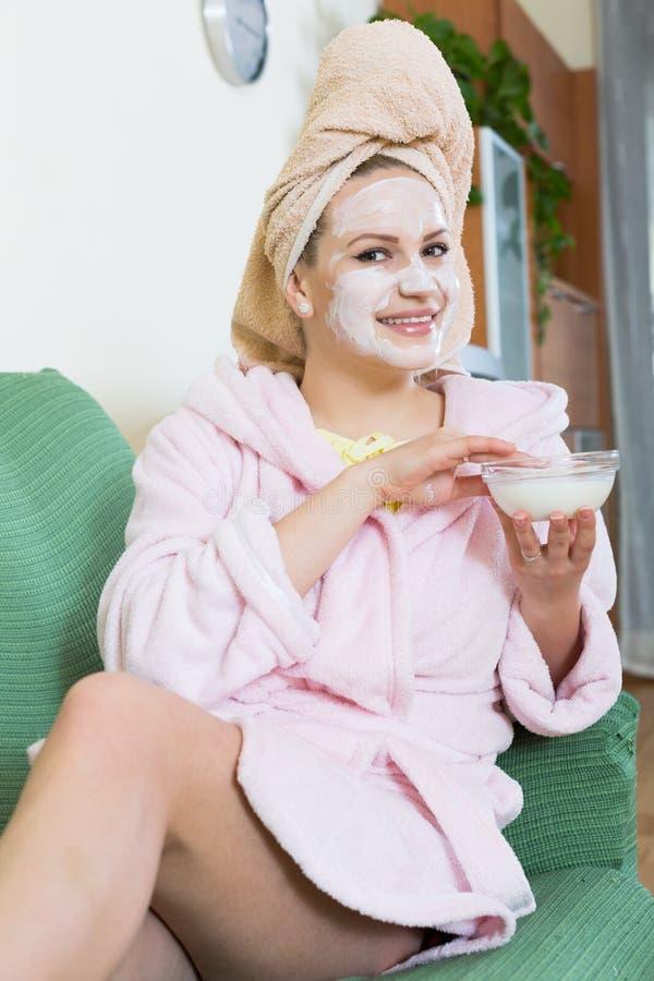 Blondin med ansiktsmask som inomhus kopplar av på soffan fotografering för bildbyråer