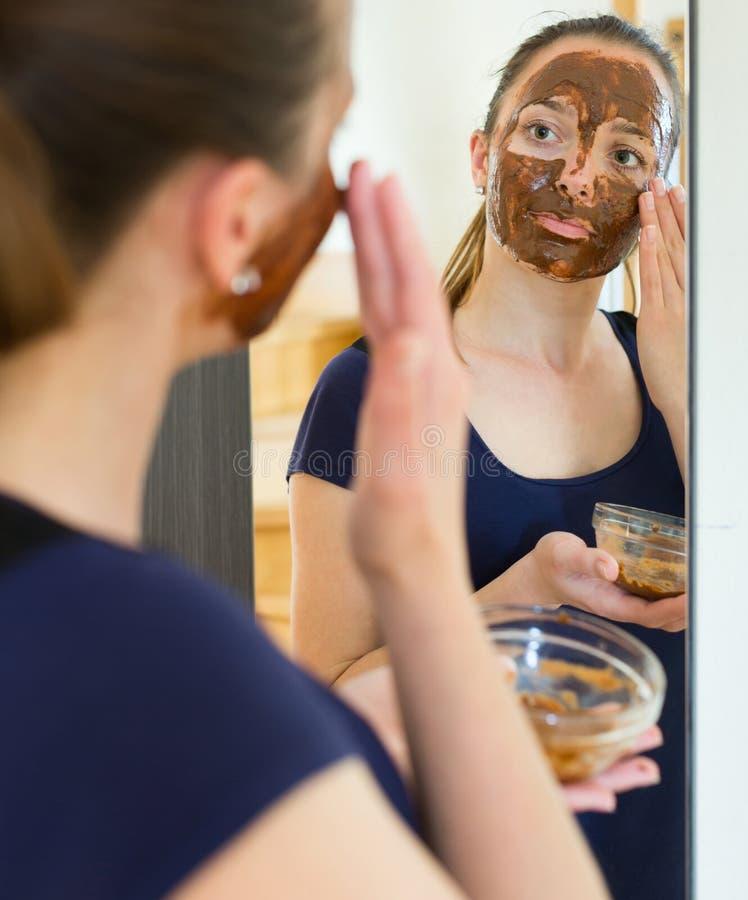Blondin med att koppla av för ansiktsmask royaltyfri foto
