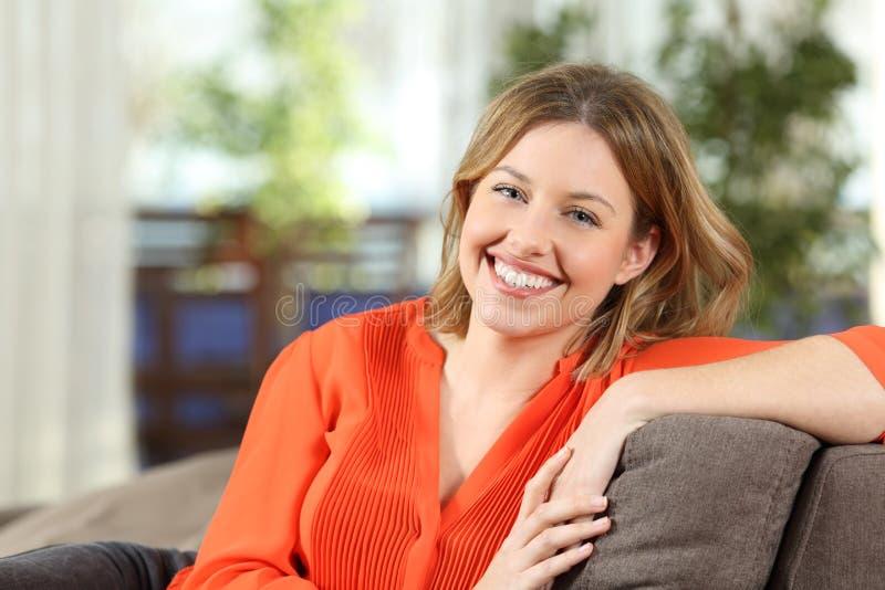Blondin med det perfekta leendet som hemma poserar arkivfoto