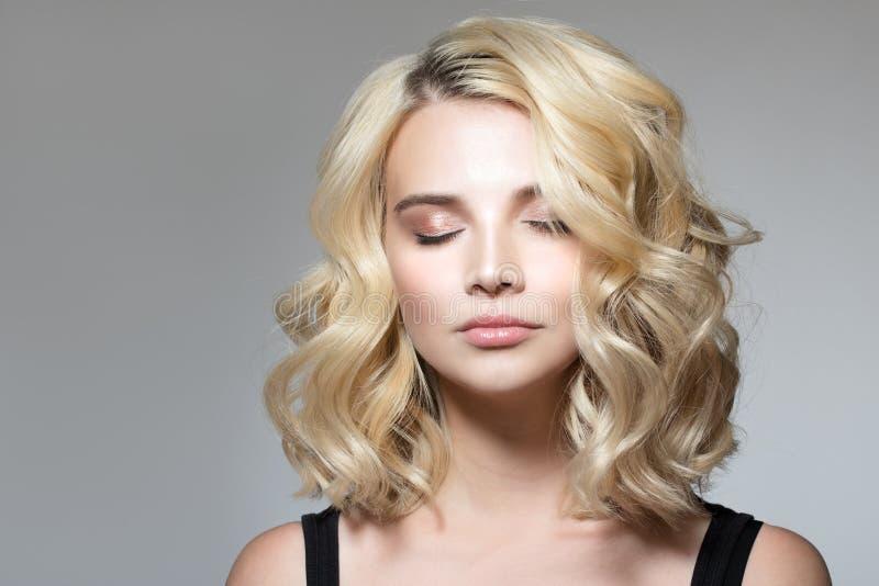 Blondin med krullning på en grå bakgrund arkivbilder