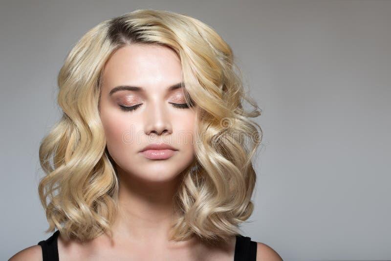 Blondin med krullning på en grå bakgrund royaltyfri fotografi