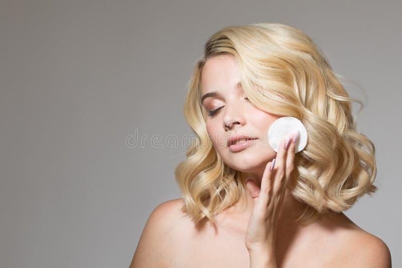 Blondin med krullning på en grå bakgrund royaltyfri foto