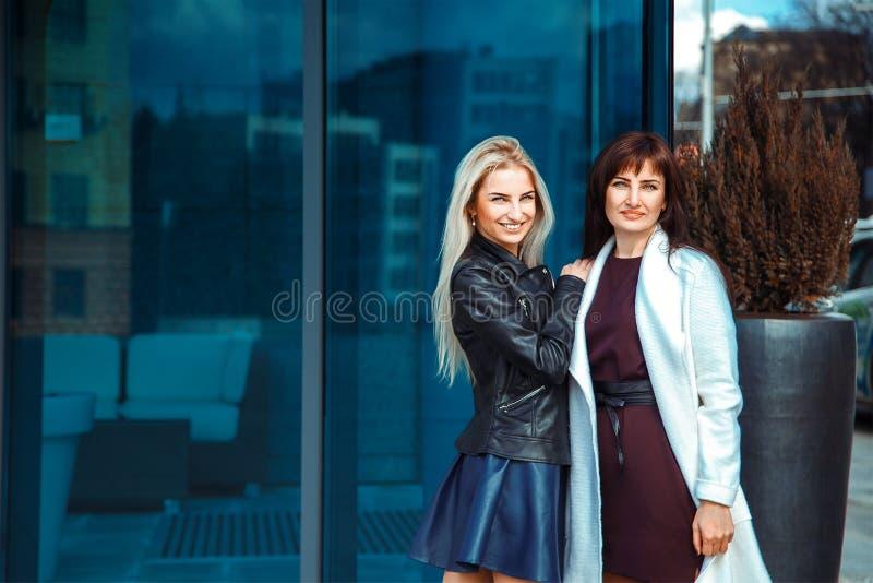 Blondin och brunett för två härlig kvinnor som utomhus poserar arkivfoto