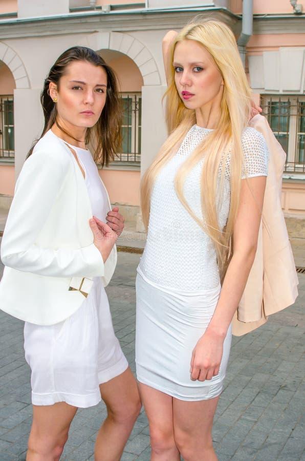 Blondin och brunett för två vänner i vita klänningar som poserar på gatan av den gamla staden royaltyfri fotografi