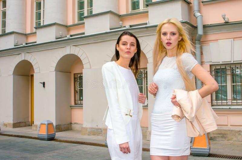 Blondin och brunett för två vänner i vita klänningar som poserar på gatan av den gamla staden fotografering för bildbyråer
