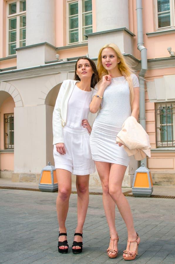 Blondin och brunett för två vänner i vita klänningar som poserar på gatan av den gamla staden royaltyfri foto