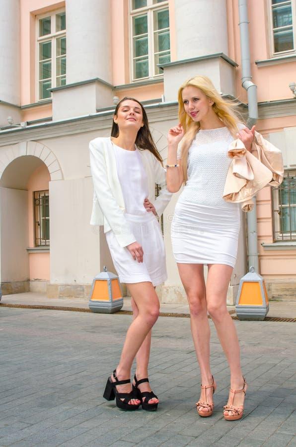 Blondin och brunett för två vänner i vita klänningar som poserar på gatan av den gamla staden arkivfoto