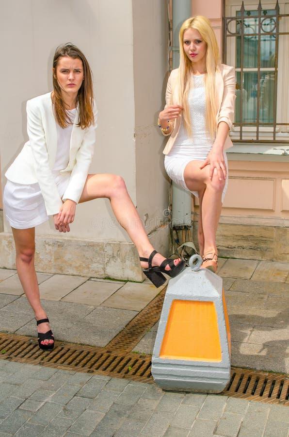 Blondin och brunett för två vänner i vita klänningar som poserar på gatan av den gamla staden royaltyfri bild