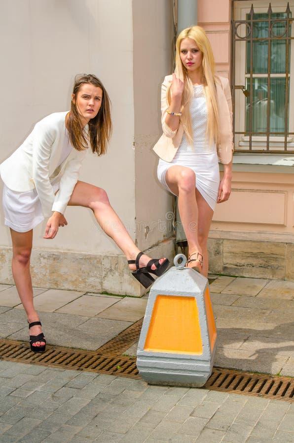 Blondin och brunett för två vänner i vita klänningar som poserar på gatan av den gamla staden arkivbild