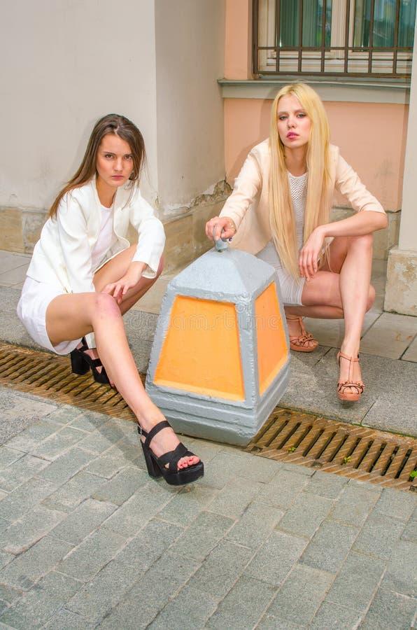 Blondin och brunett för två vänner i vita klänningar som poserar på gatan av den gamla staden royaltyfria bilder