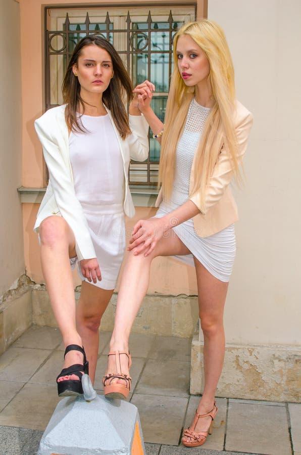 Blondin och brunett för två vänner i vita klänningar som poserar på gatan av den gamla staden arkivbilder