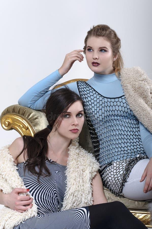 Blondin och brunett som poserar i studion arkivbild