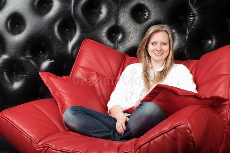 Blondin på en röd soffa arkivfoton