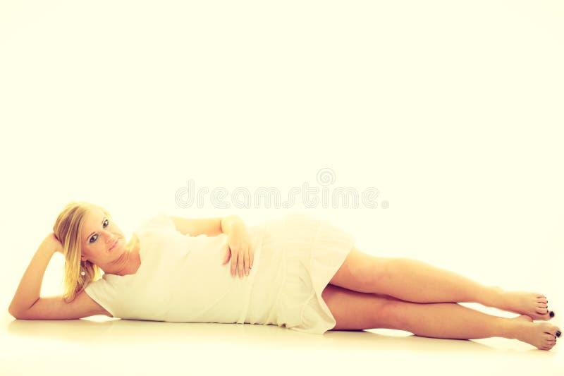 Blondin som bedövar den unga damen i vit royaltyfri foto