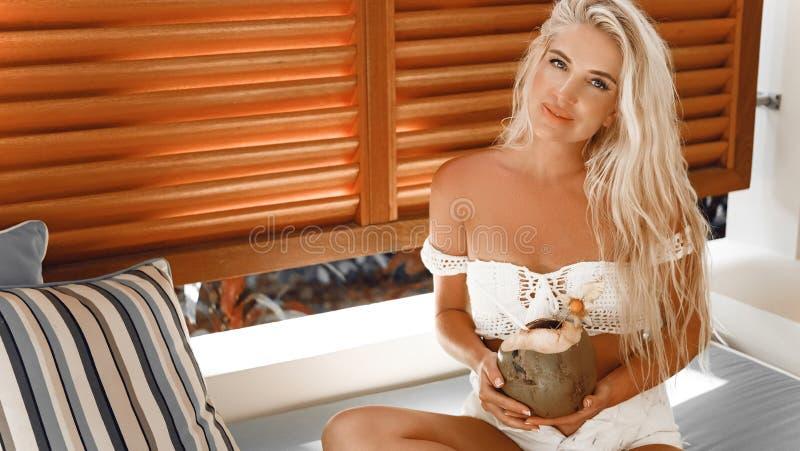 Blondine in der weißen Badebekleidung mit Kokosnuss coctail, das auf Sofa am Luxuslandhaus durch tropischen Strand, Sommer vactio stockbilder