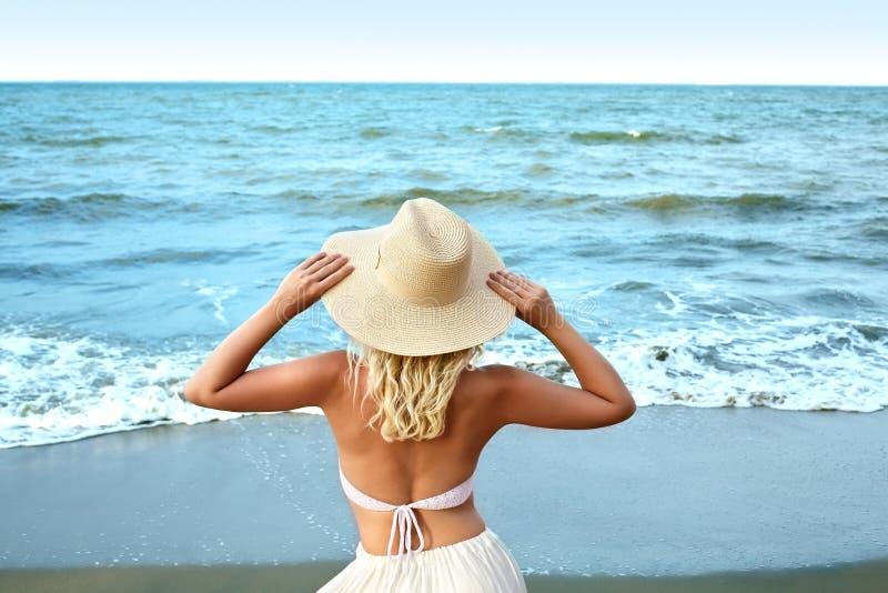 Blondine in der weißen Sommer-Art, die in Meer steht und Hut hält Luxuslebensstil-hintere Ansicht Reisenkoffer mit Meerblick nach stockbild