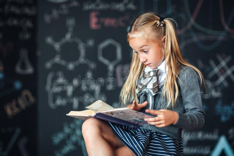 Blondine des kleinen Mädchens in den Schuluniformblicken auf das Buch mit einem überraschten Gesicht Tafel mit Schulformeln Kompl stockbild