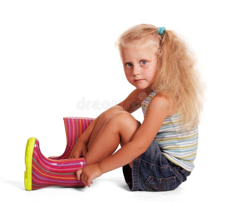 Blondine des kleinen Mädchens kleidete die Gummistiefel, die auf Weiß lokalisiert wurden stockfotografie