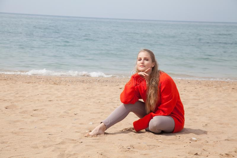 Blondine, die allein auf einem sandigen Strand sitzen stockfotos